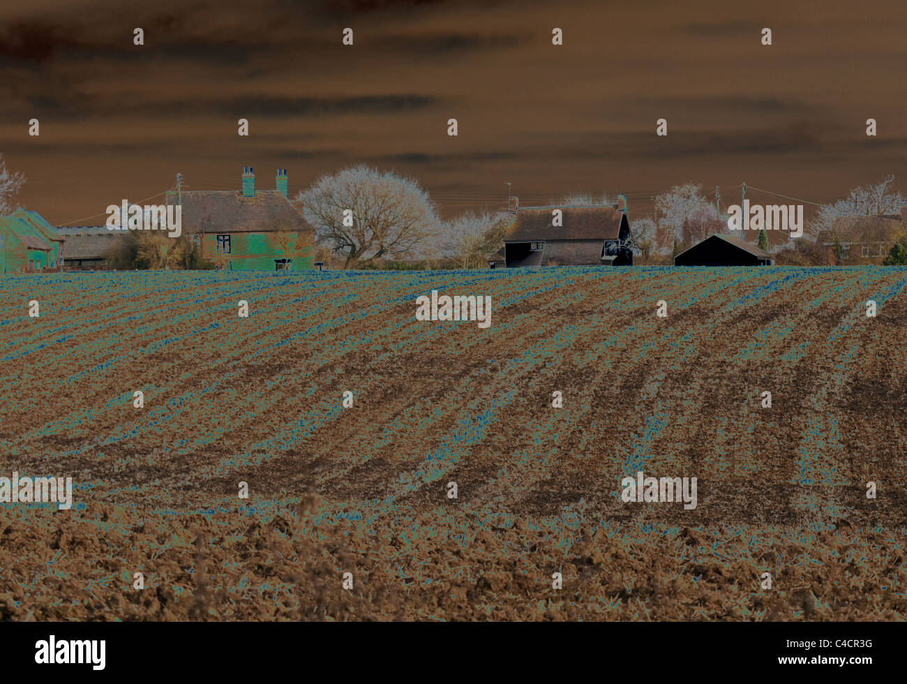 Solarised photograph of a ploughed field and farm buildings - Stock Image