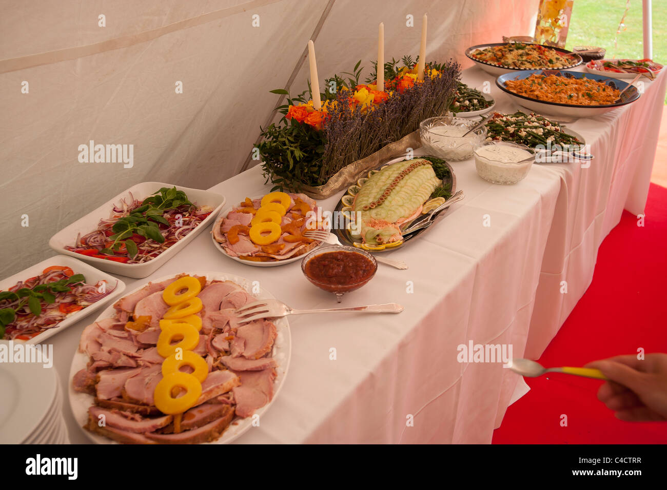Tables laid out with food for a party in a marquee - Stock Image