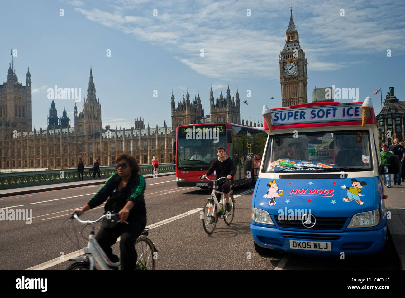 Westminster Bridge, London, with Big Ben, Houses of Parliament, Ice Cream van, red bus and cyclists - Stock Image