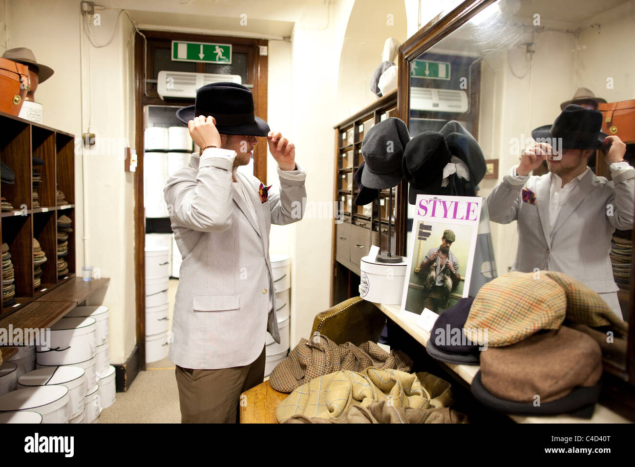 654c9d1a Man trying fedora hats at Lock & Co hatters, St.James's Street, London