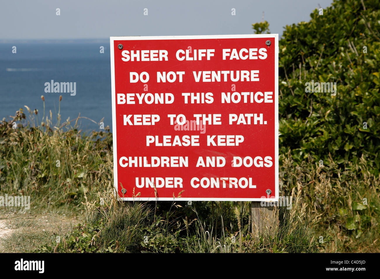 Sheer cliff red danger warning sign on cliffs on the Isle of Wight, England - Stock Image