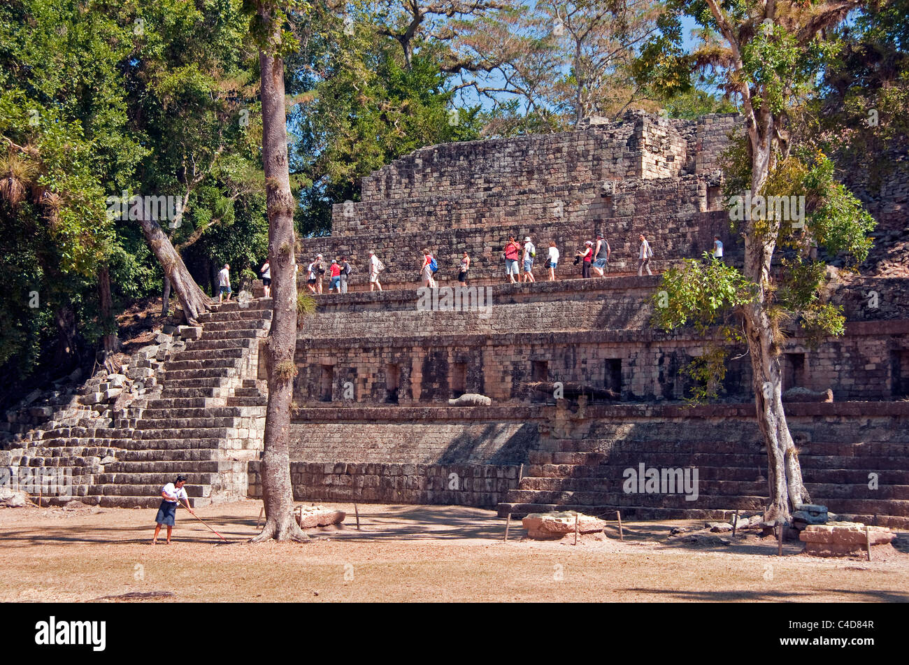 Tourists crossing the Temple of the Inscriptions on the West Court Acropolis of Mayan ruin of Copan - Stock Image