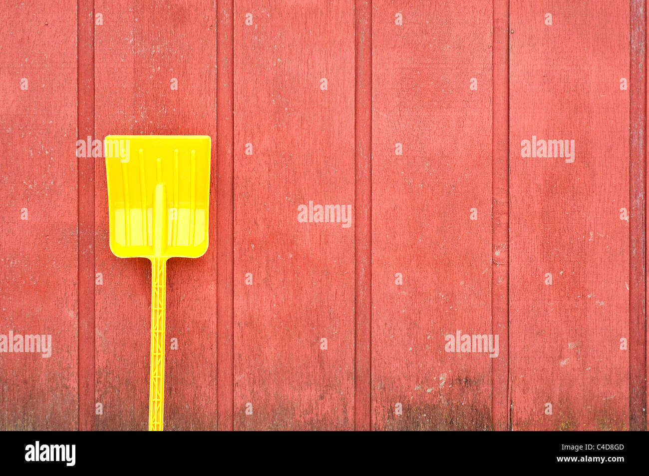 A plastic yellow toy shovel leans against a red wooden barn wall - Stock Image