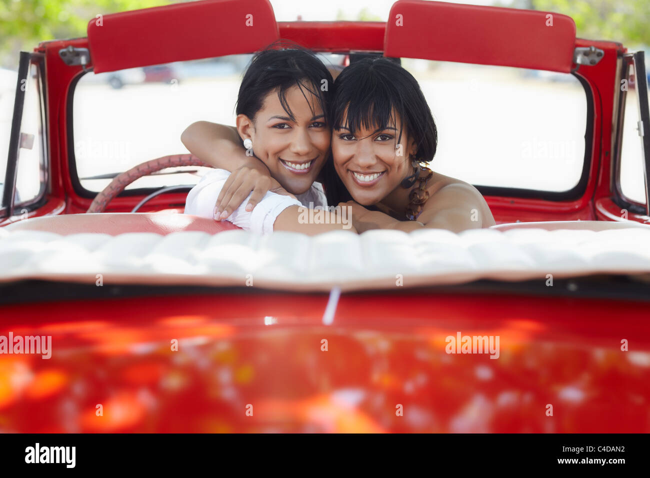 young adult brunette twin women driving convertible red car and looking over shoulders. Horizontal shape, rear view, - Stock Image