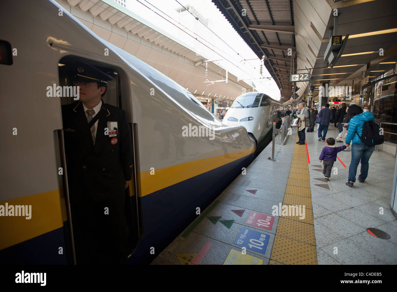 Bullet train, conductor, and passengers on platform at Tokyo station, Japan, Far East, Asia. - Stock Image