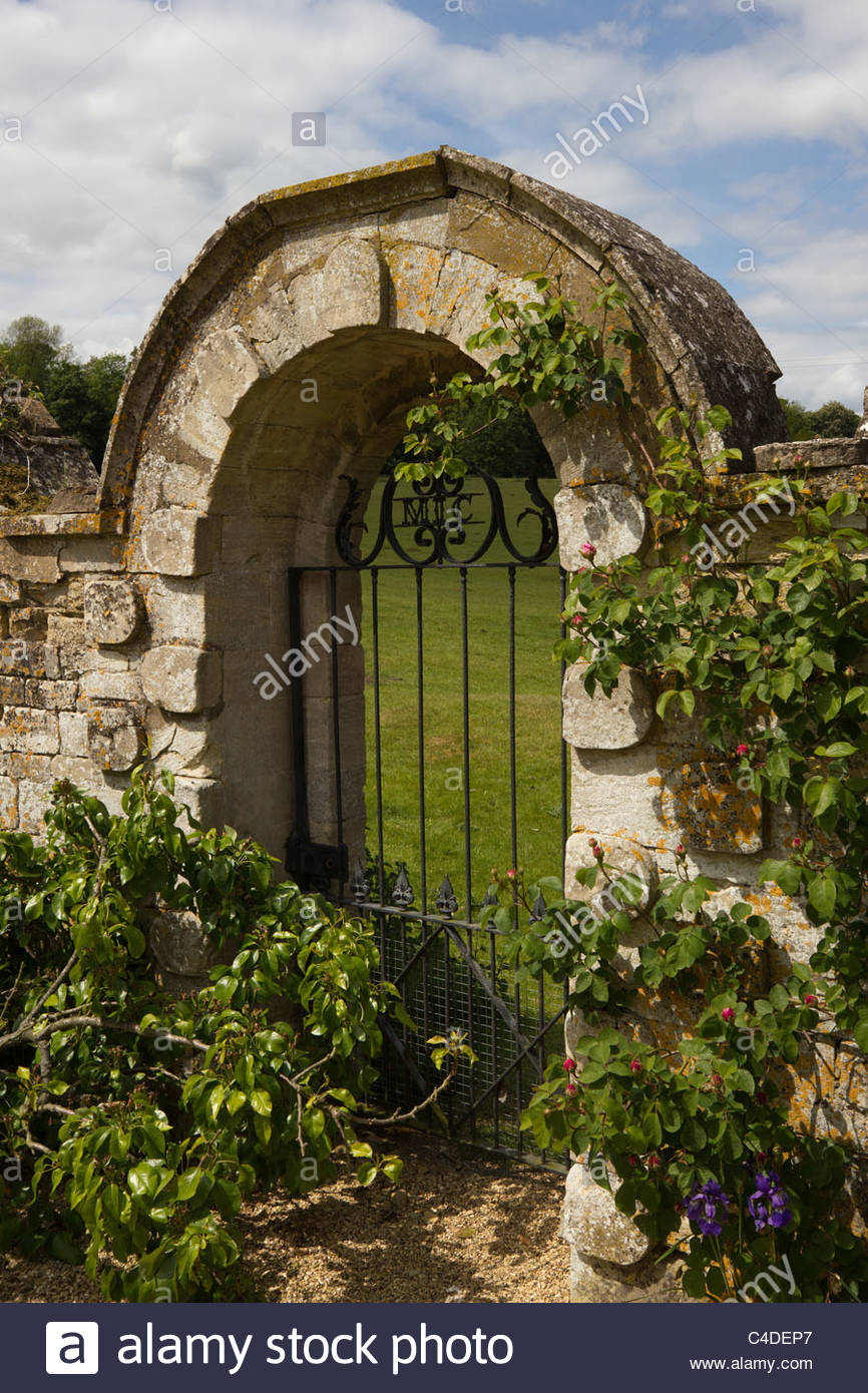 Overgrown Ornate Wrought Iron Gate In Old Stone Wall With