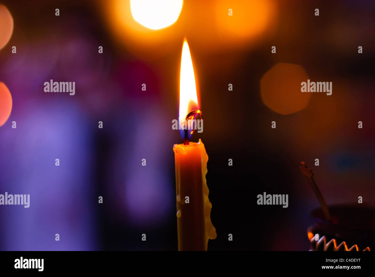 Burning candle on a blurred color background - Stock Image