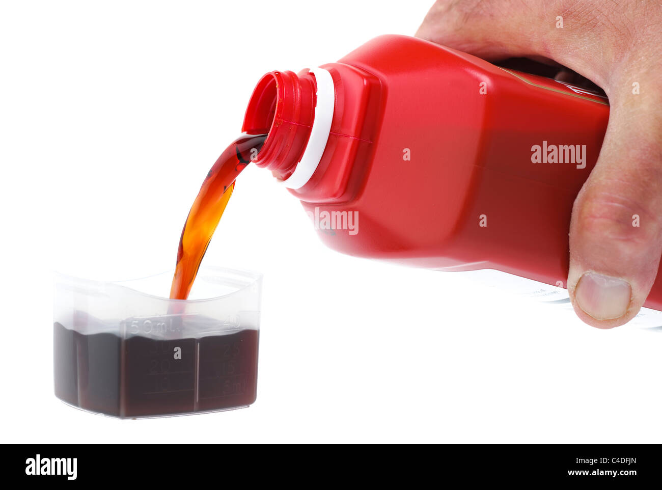 A 50 ml measure of tomato plant food being poured into a plastic measuring lid - Stock Image
