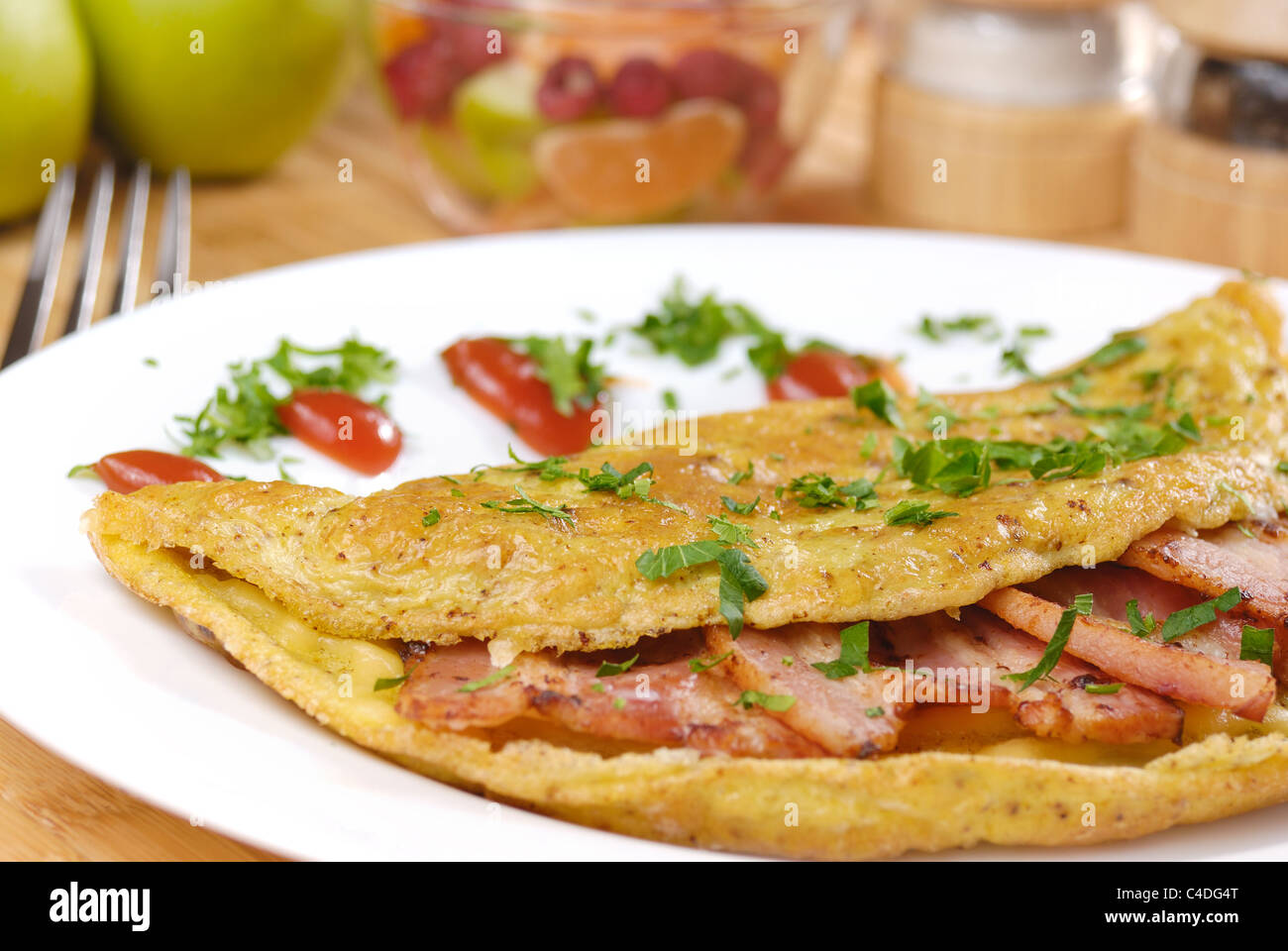 Omelet with bacon served on white plate - Stock Image