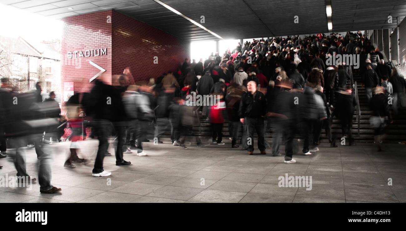 One man pauses as the crowd moves up the stairs towards Arsenal's Emirates Stadium. - Stock Image