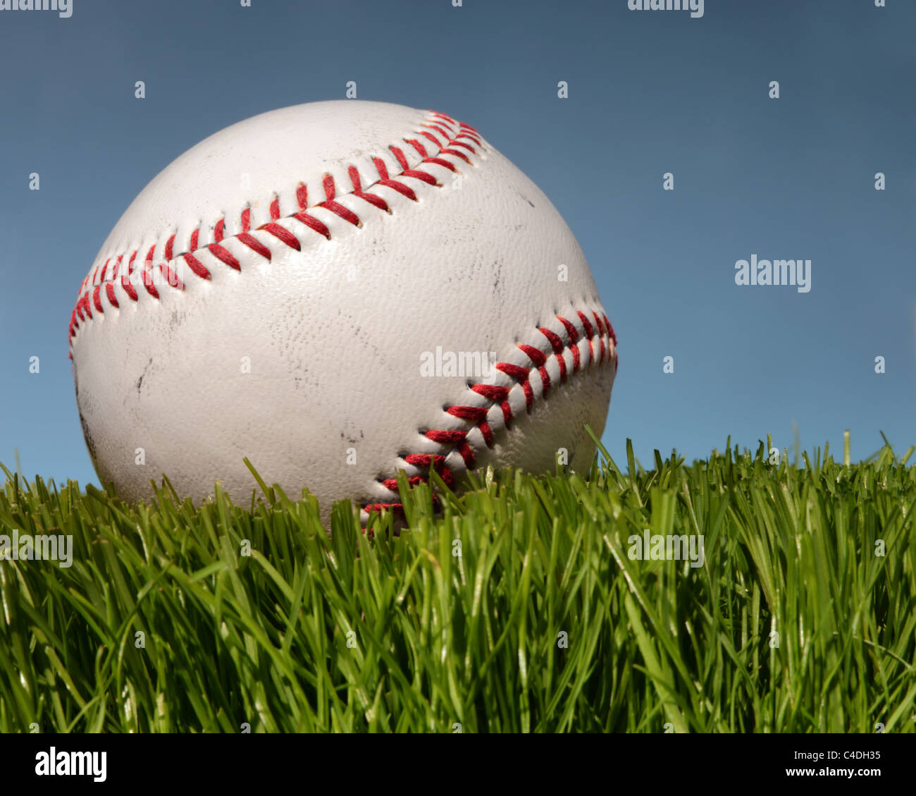 Baseball on green grass with blue sky behind. - Stock Image