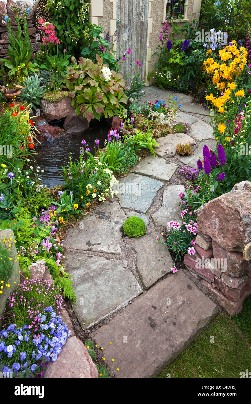 small garden with slabs as the garden path a small pool and rockery C4DH5J