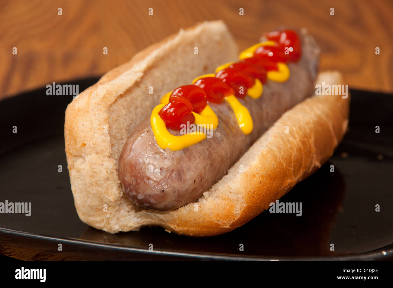 Cooked Bratwurst on a bun topped with Mustard and Ketchup Stock Photo