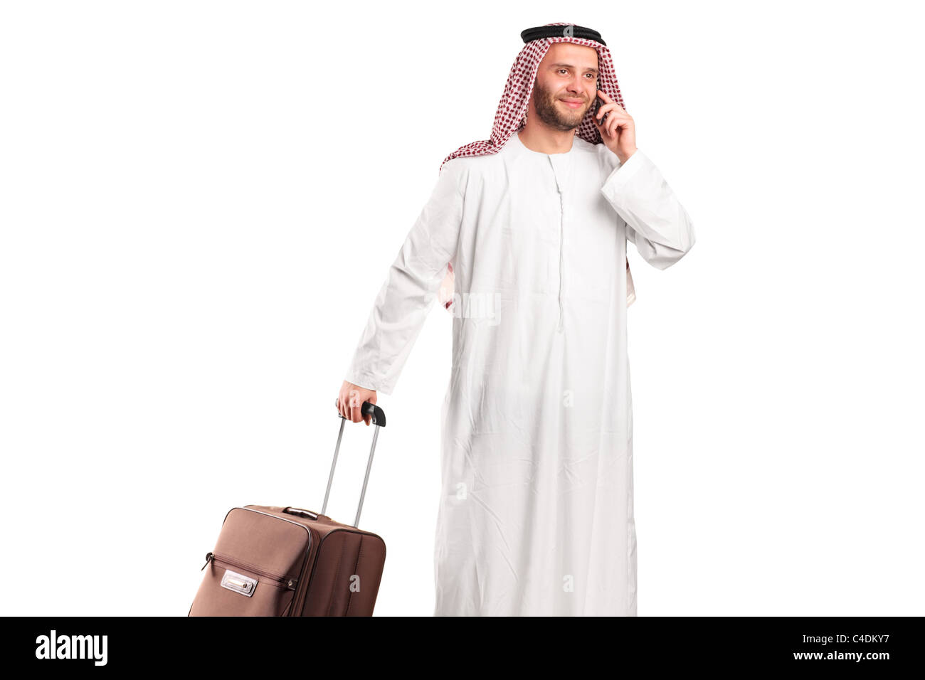 Arab tourist carrying a suitcase and talking on a mobile phone Stock Photo