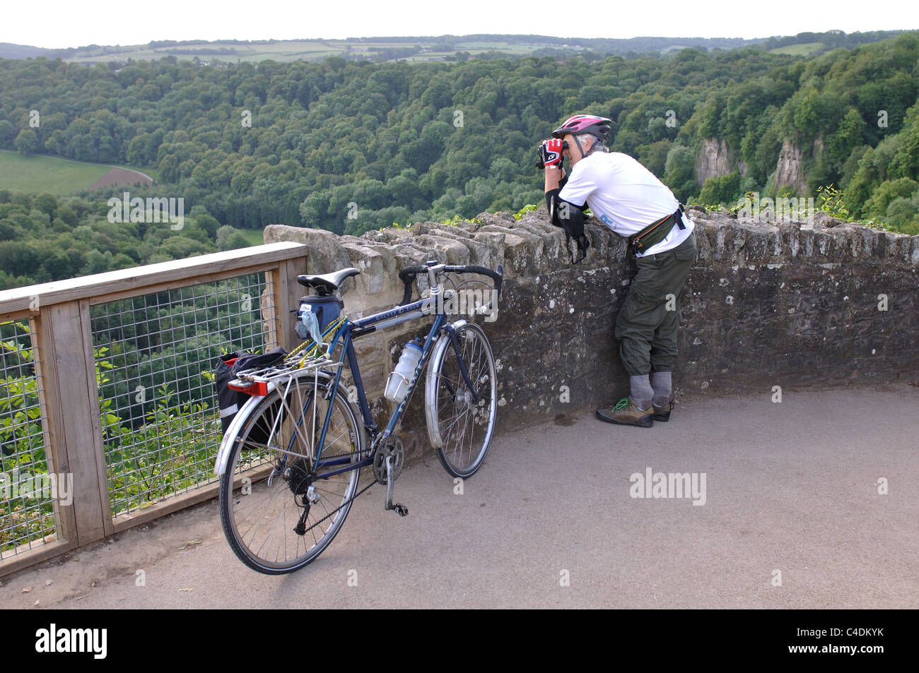 Cyclist on Yat Rock looking through binoculars - Stock Image