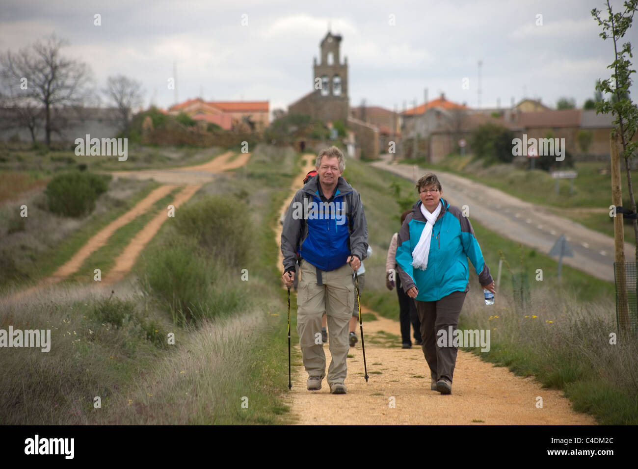A couple leaves El Ganso village in the French Way that leads to Santiago, Spain. - Stock Image