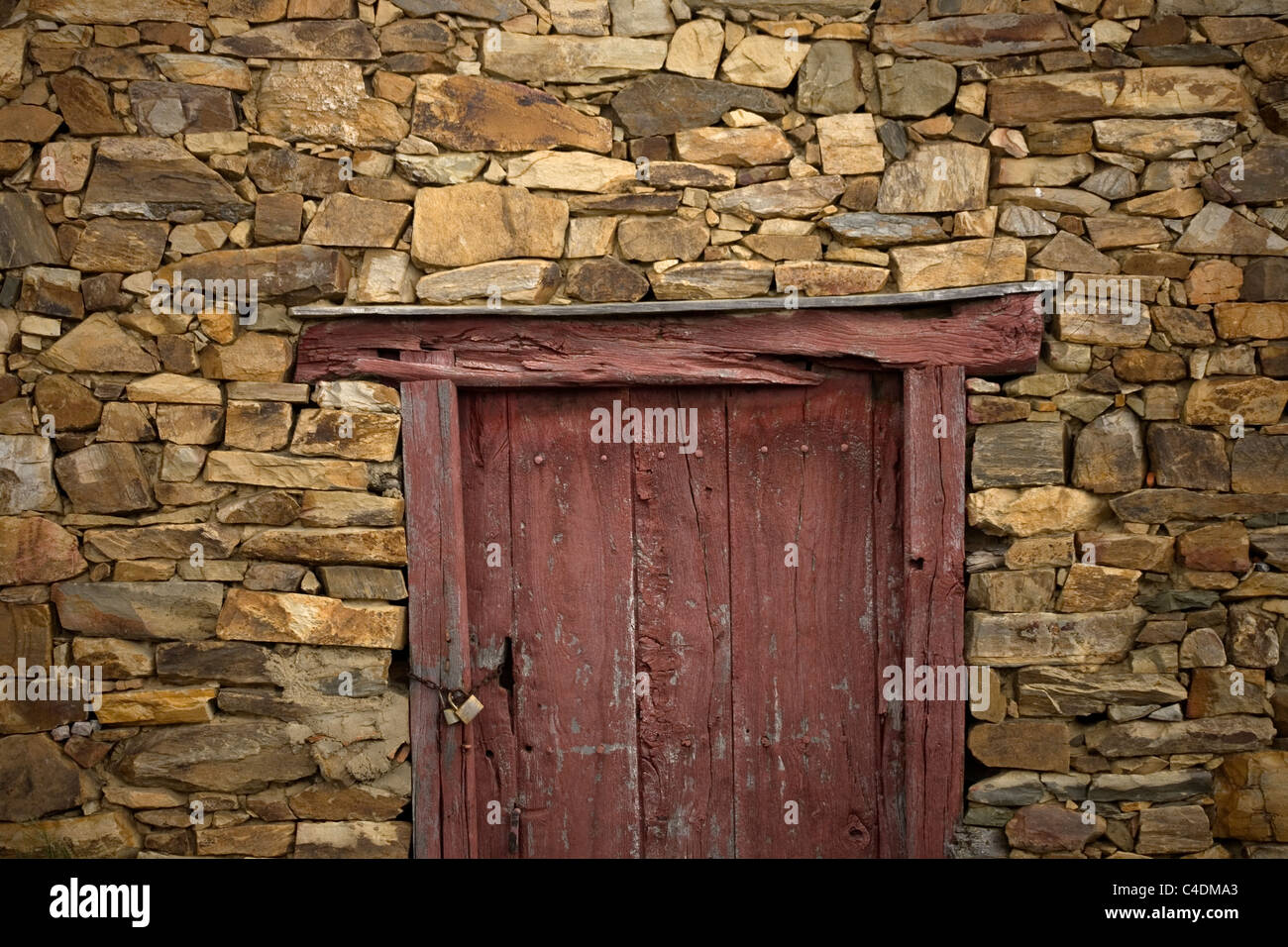 Dark red door in a stone house in the French Way that leads to Santiago, in El Ganso, Spain. - Stock Image