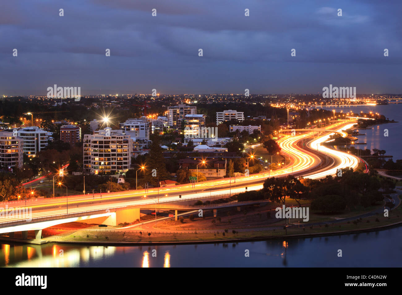 Busy road at night beside houses and apartment buildings. - Stock Image