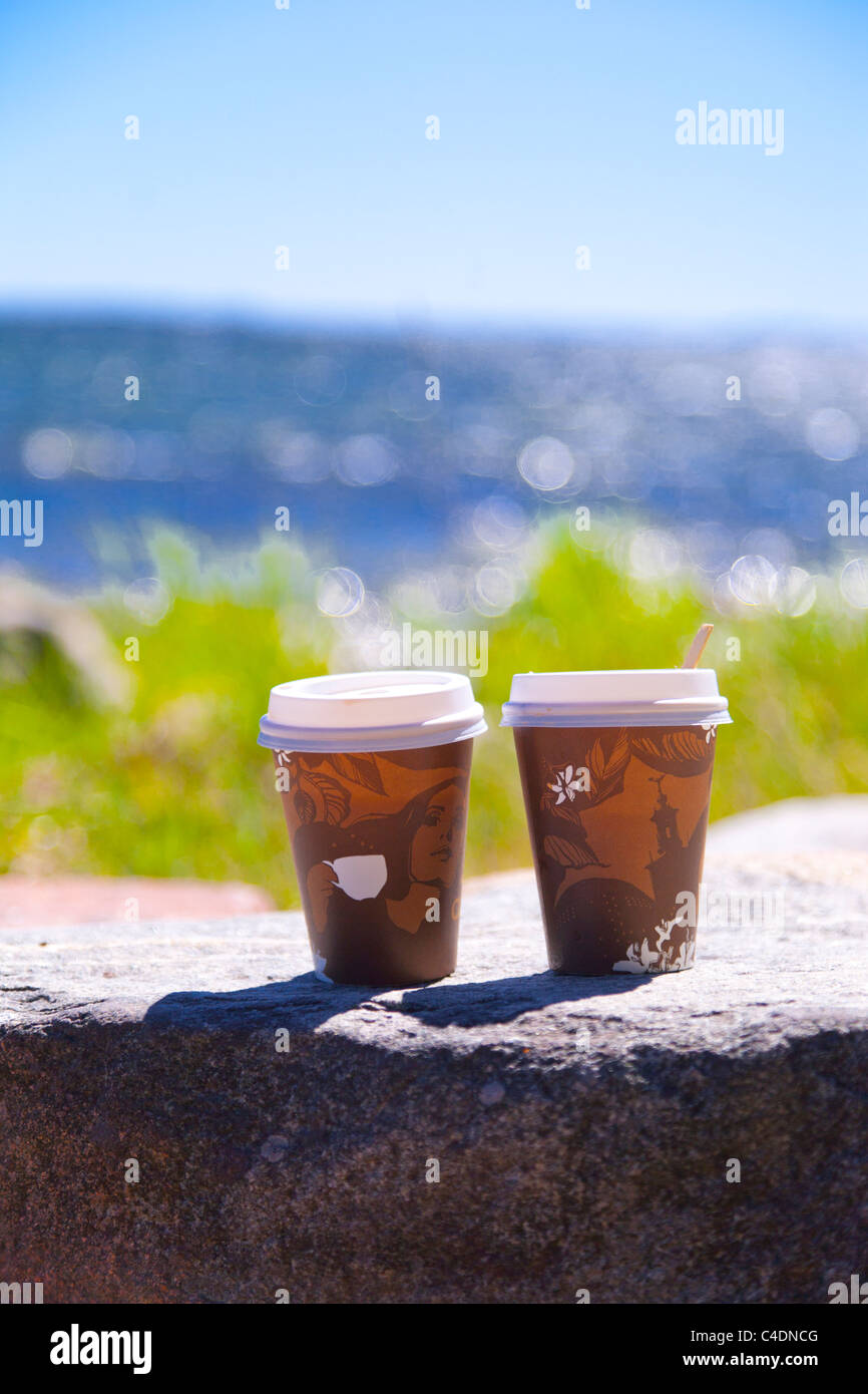 Two coffe mugs on a stone by the sea. - Stock Image