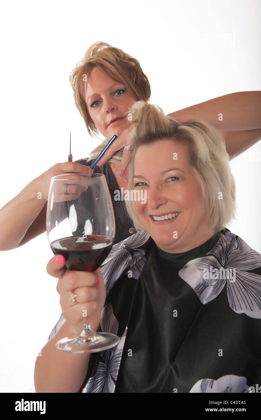 Hair stylist working on female customer with glass of red wine - Stock Image