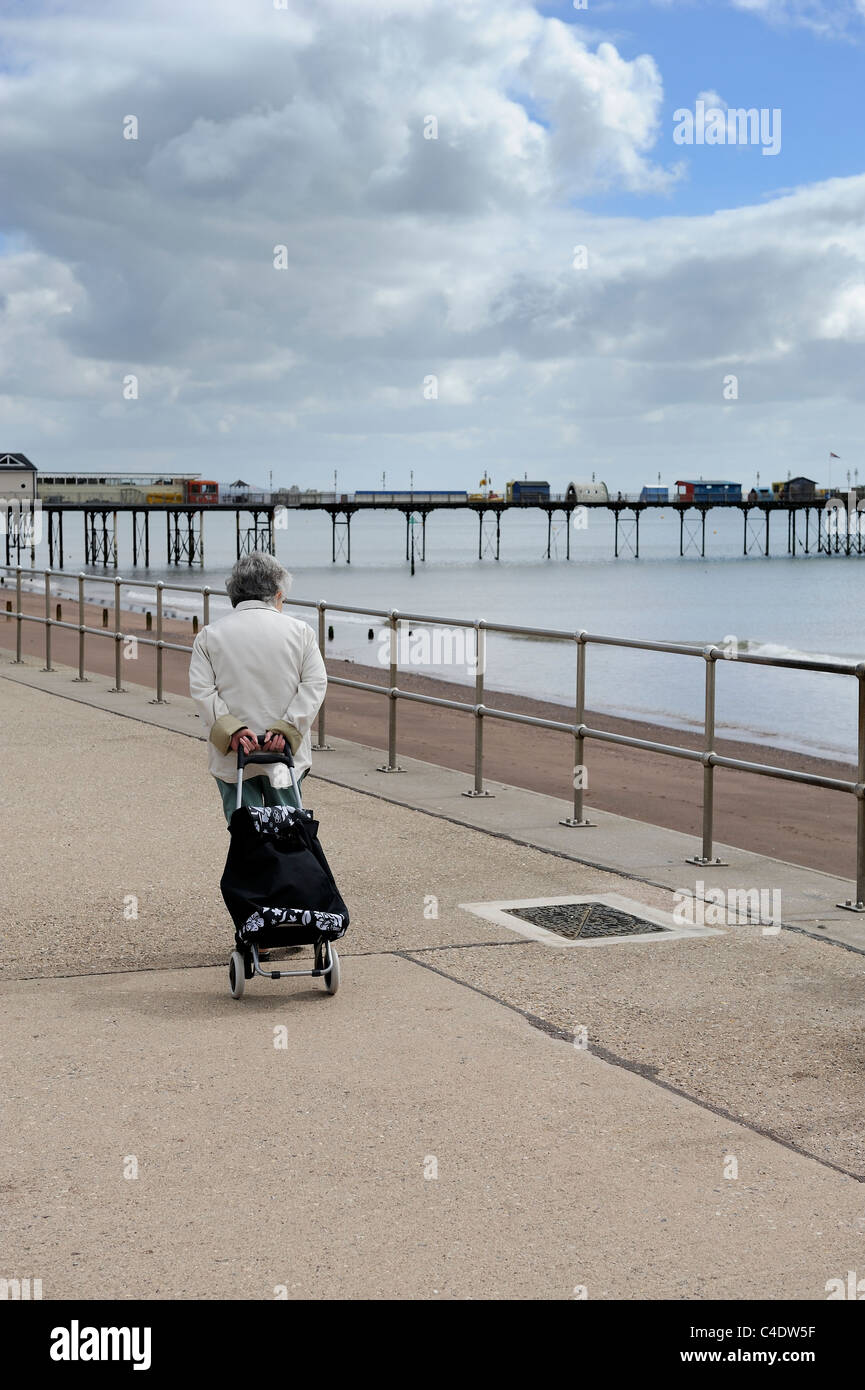 old lady with shopping trolley walking along sea front teignmouth devon england uk - Stock Image