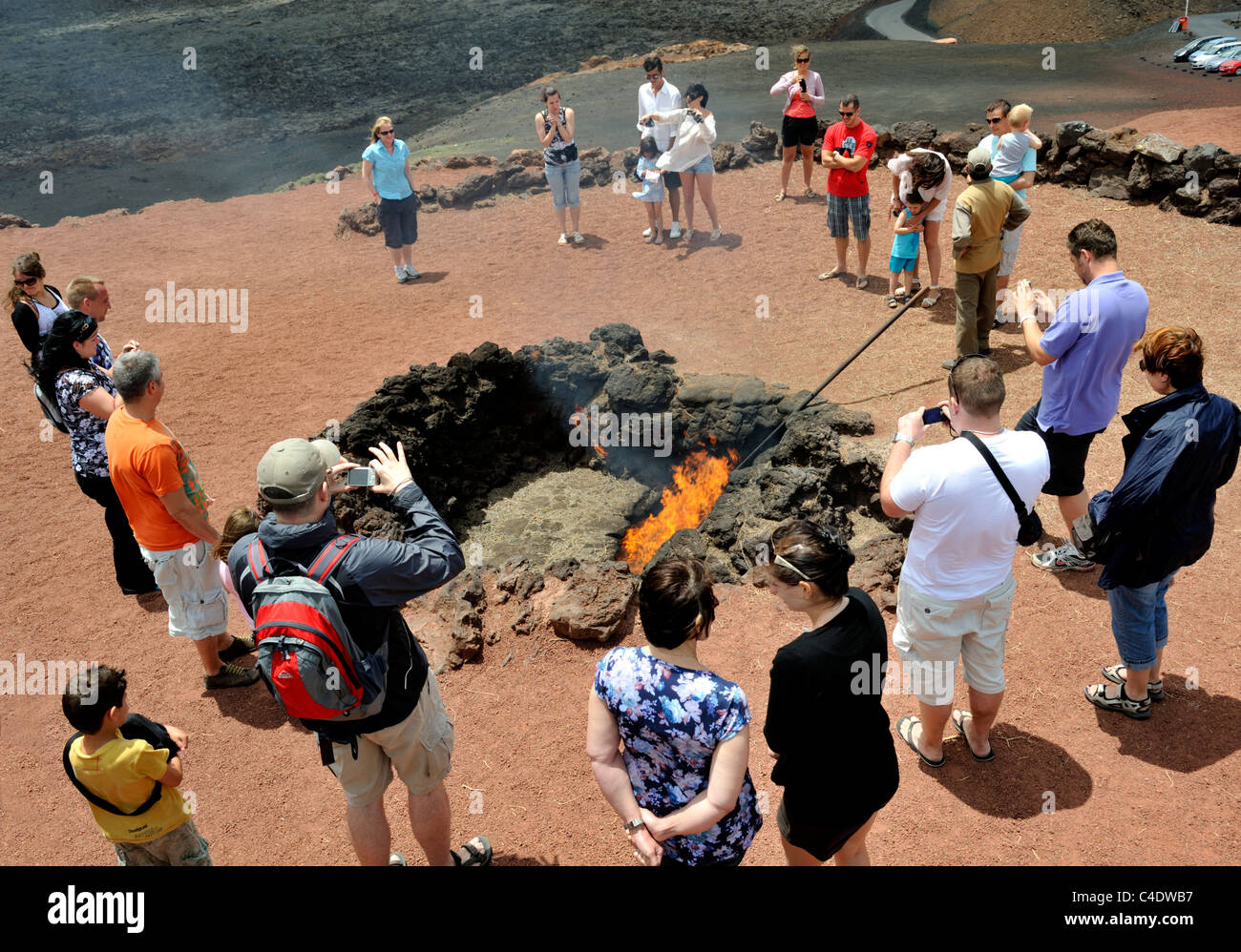 Tourists watching volcanic heat set fire to dry lichen Timanfaya park, Lanzarote, 'Canary Islands' - Stock Image