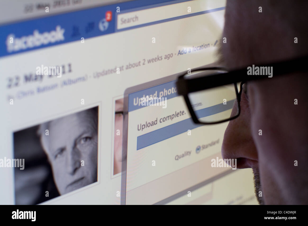 Uploading photos to facebook, facebook now employs face recognition software - Stock Image