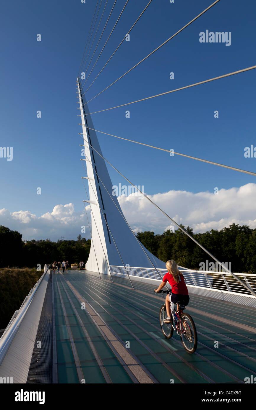 Woman riding bicycle on Sundial Bridge at Turtle Bay, Redding, California. Designed by Santiago Calatrava. - Stock Image
