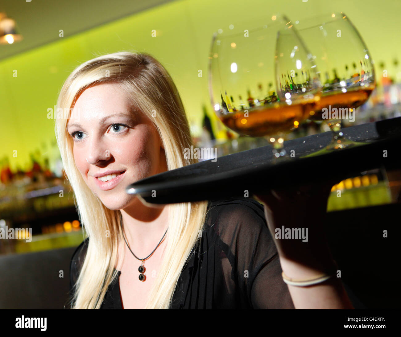 Waitress in a cocktail bar carrying a tray of brandy balloon glasses - Stock Image