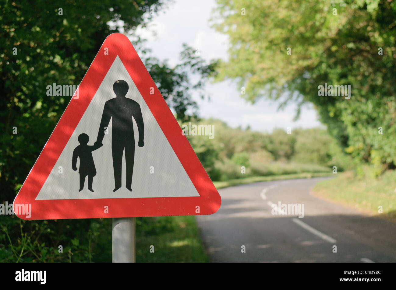 Triangular sign warning drivers of the presence of pedestrians on a narrow rural road - Stock Image