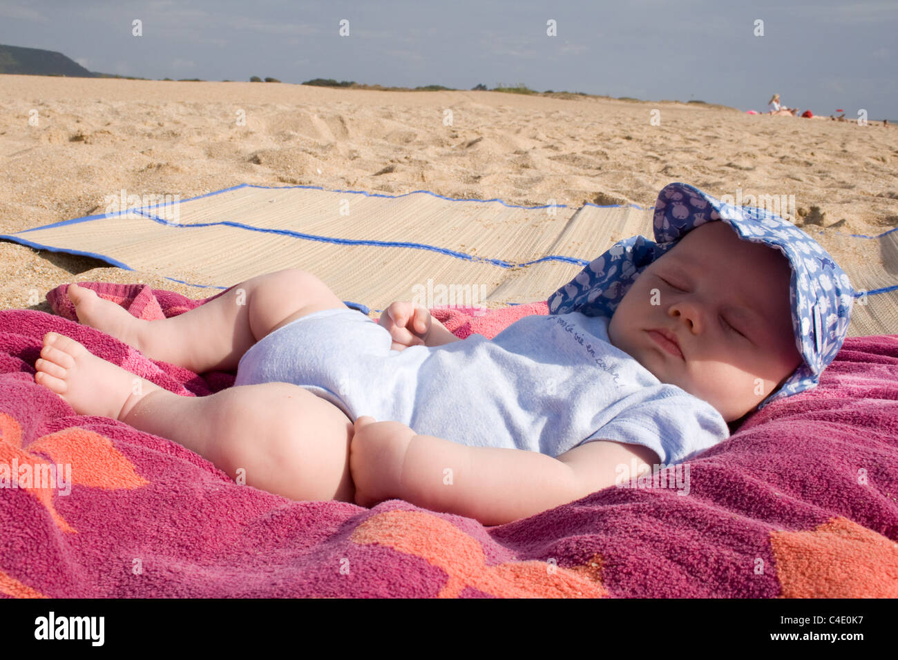 3 month old baby having his nap on the beach Stock Photo
