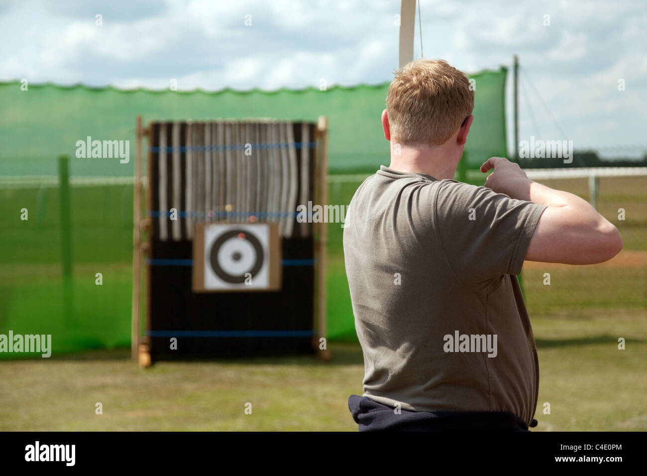 An overweight man firing at a target with a bow and arrow - Stock Image