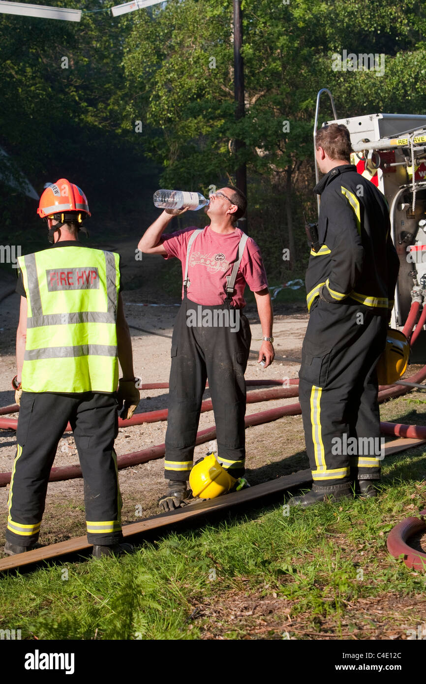 Firefighter taking well earned drink during Swinley Forest fire close to Broadmoor, Crowthorne, Bracknell - Stock Image