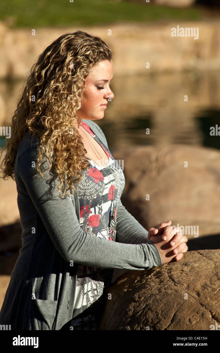Relaxing relaxed Teen girl 15-17 year old olds praying meditating thinking reflecting reflects ponders pondering - Stock Image