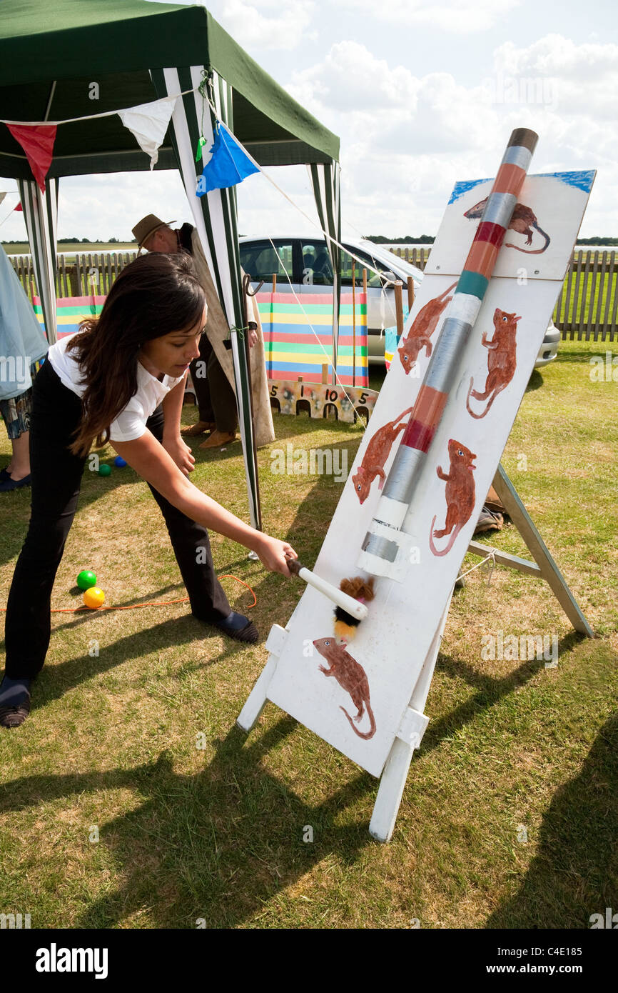 A teenage girl playing 'Splat the rat',  Newmarket town carnival Suffolk UK - Stock Image