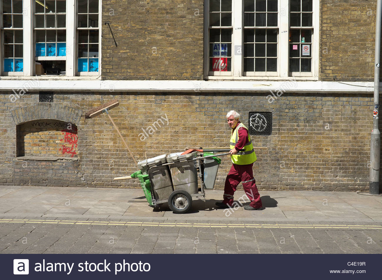 Municipal street cleaner with his mobile bin trolley, in Brick Lane, London, UK. Stock Photo