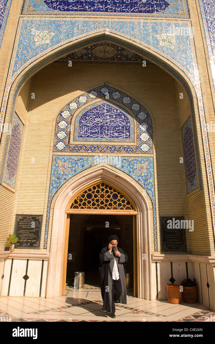 Shi'ite Cleric exiting mosque whilst using mobile phone, Baalbek, Bekaa Valley, Lebanon. - Stock Image