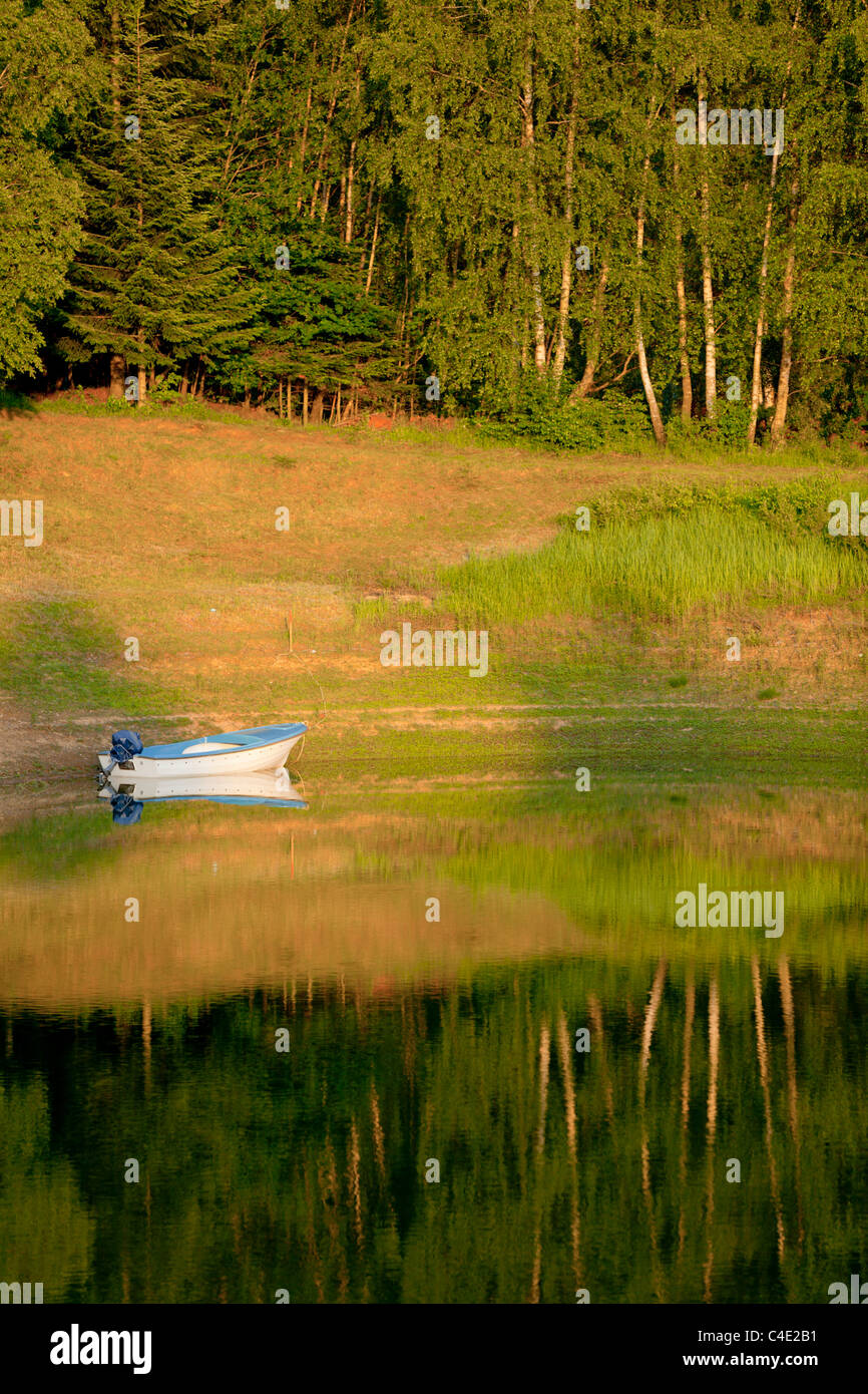 Moored boat at sunset time Lokve lake in Gorski Kotar Croatia countryside tranquillity tranquil unwind spot lakeside nature alpfabet forest Green Stock Photo