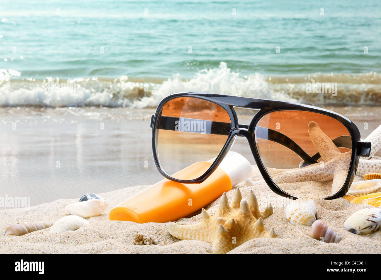 Sun glasses and bottle of balm solar on sandy beach. - Stock Image