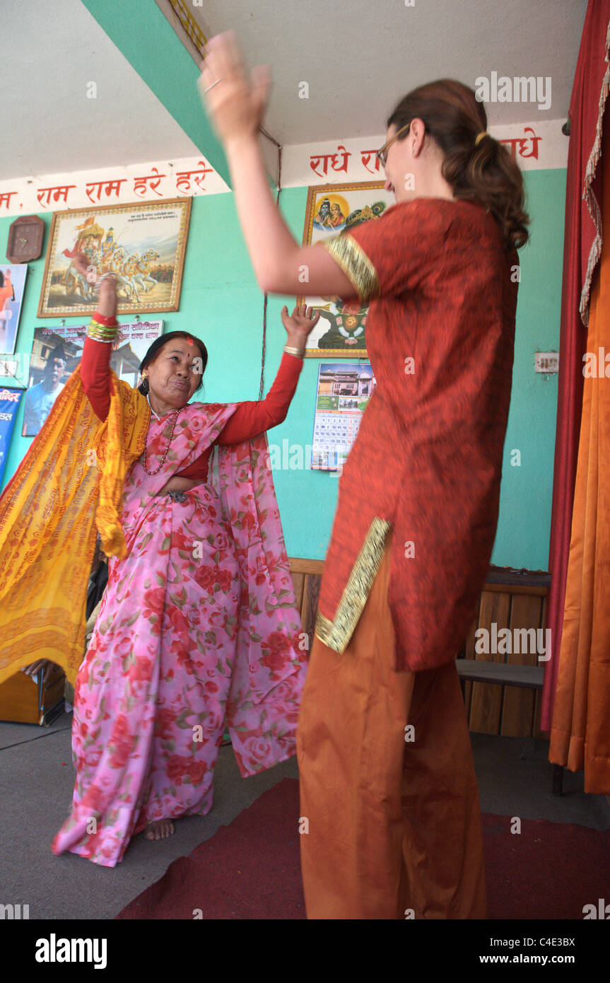 A western woman dancing with an old Nepali woman - Stock Image