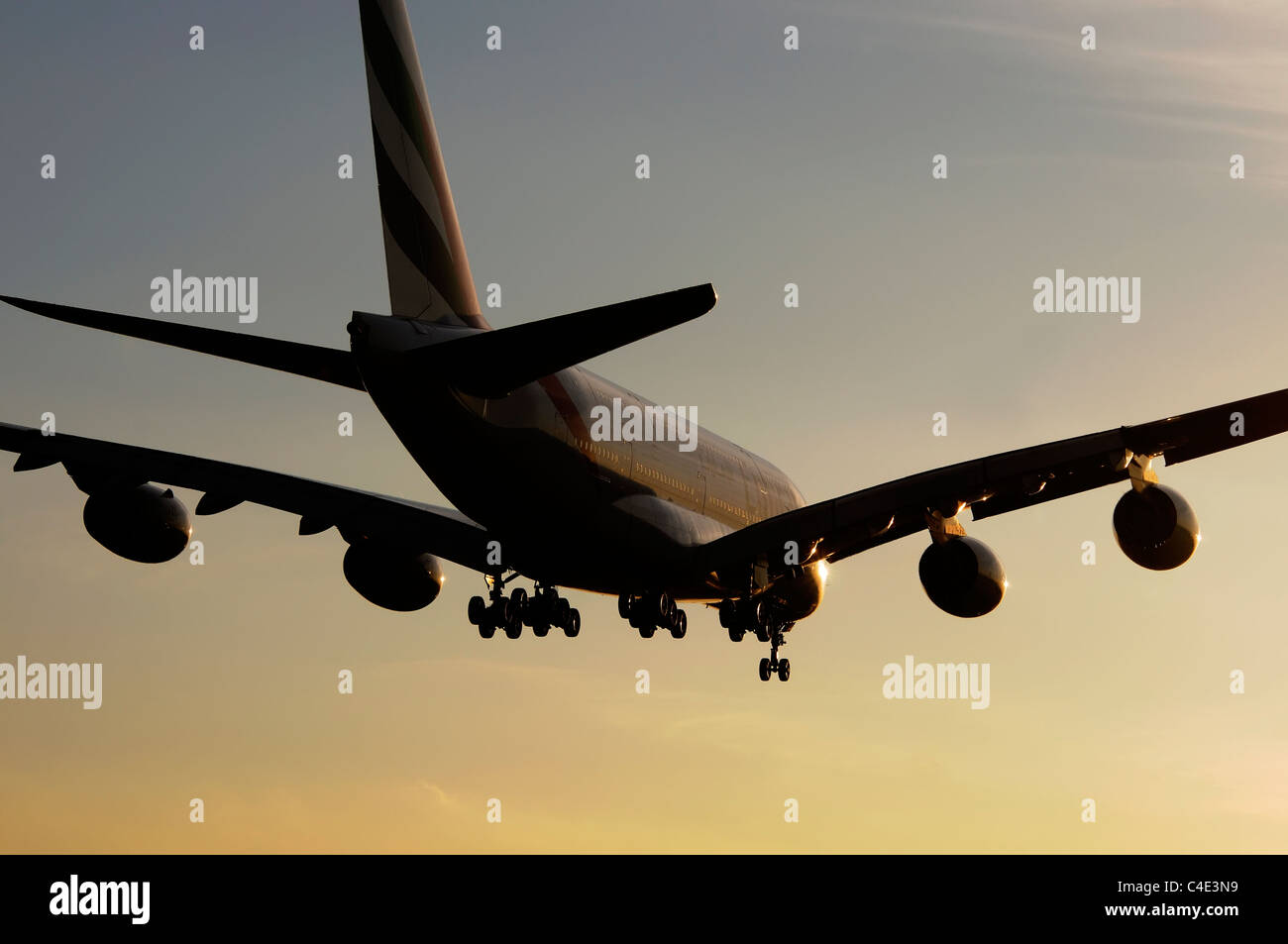 The Airbus A380 landing in the sunset - Stock Image