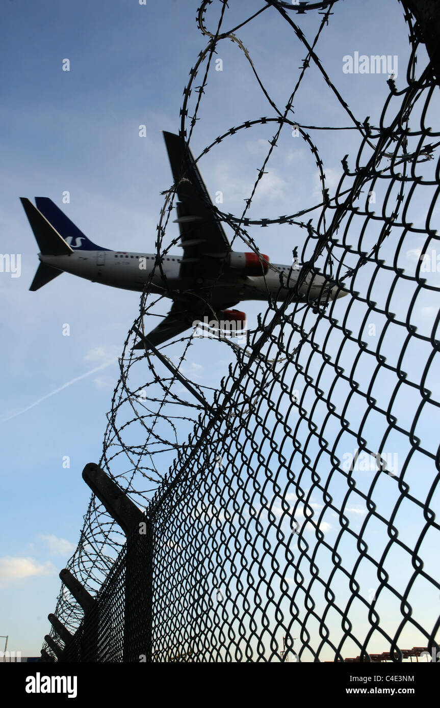 A landing plane crossing the barbed wire perimeter fence at Heathrow Airport - Stock Image