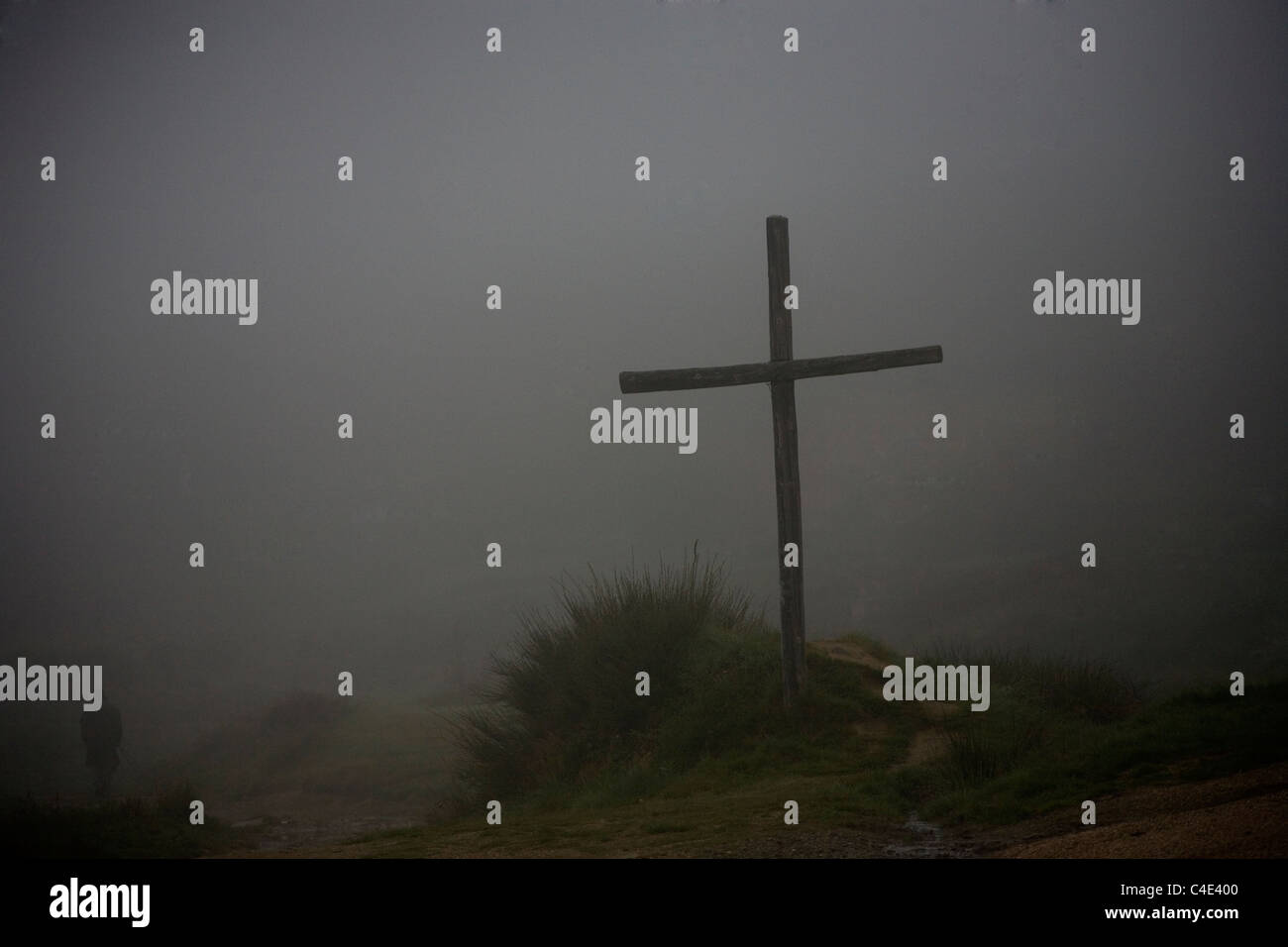 A pilgrim passes a cross made of wood as he walks in the French Way of St. James Way, Foncebadon village, El Bierzo - Stock Image