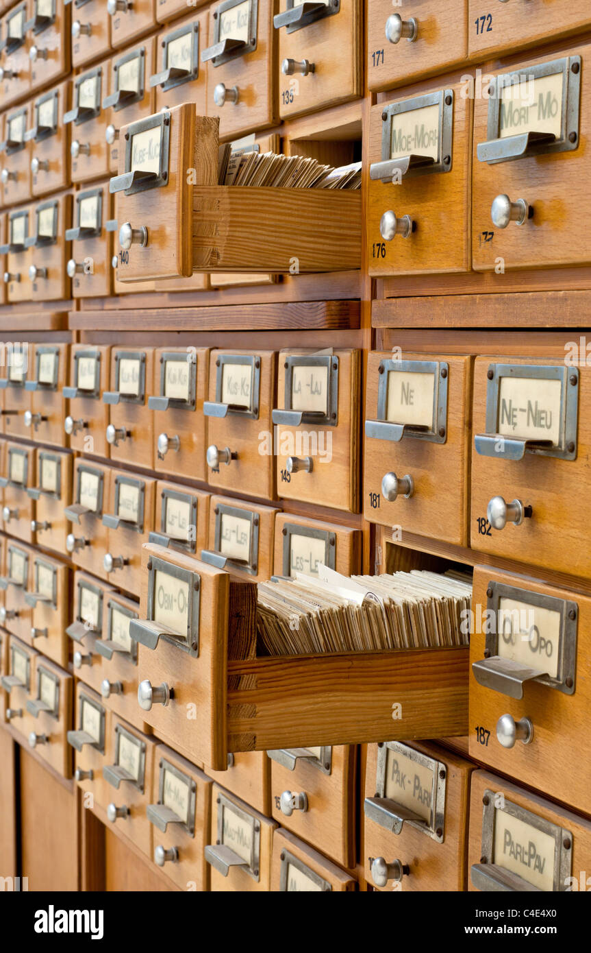 An old card catalogue in a library with two drawers opened - Stock Image