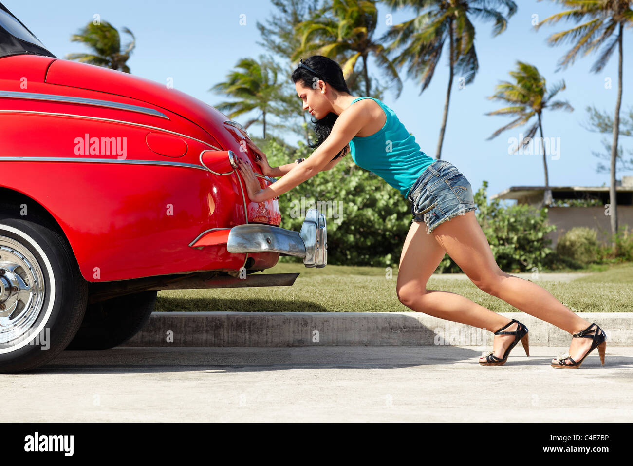 young hispanic woman pushing broken down red convertible vintage car. Horizontal shape, full length, side view - Stock Image