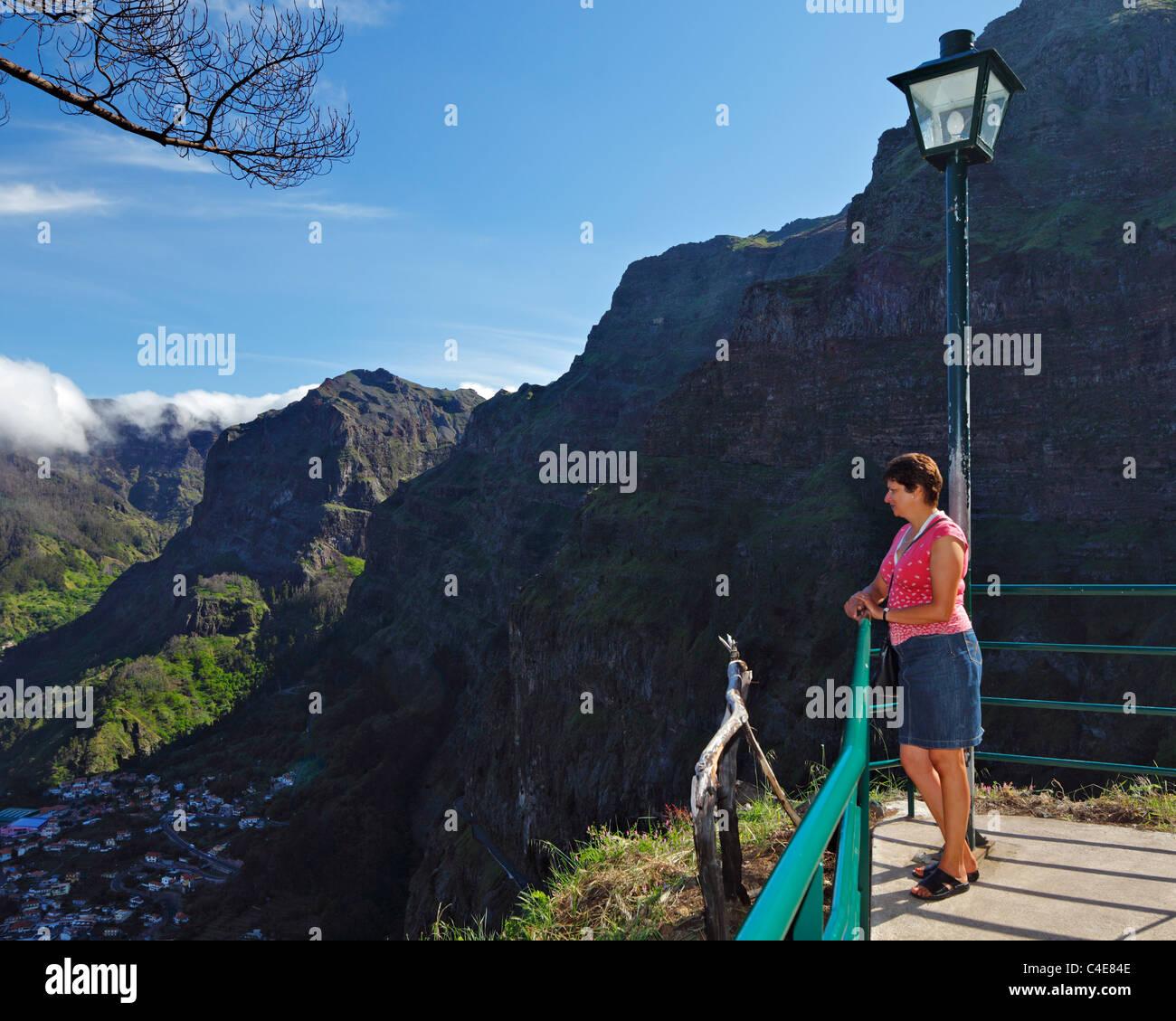 Woman looking at the Village of Curral das Freiras from Eira do Serrado, Madeira. - Stock Image