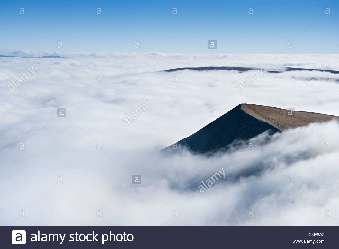 Hikers on the summit of Cribyn, rising above a sea of cloud. Brecon Beacons National Park, Powys, Wales. - Stock Image