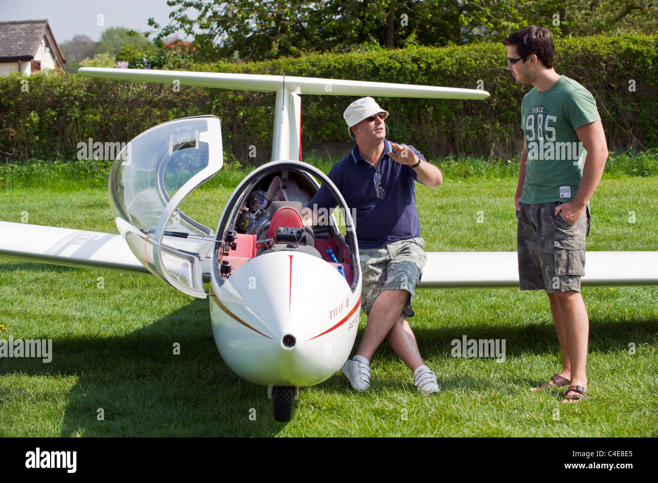 Young man receiving instruction before having first flight in two seater glider aircraft - Stock Image