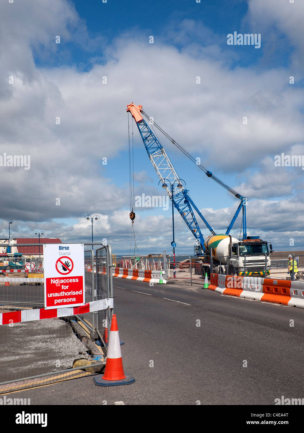 A crawler crane erecting pre-cast concrete sections of a new sea wall at Redcar Cleveland North Yorkshire June 2011 Stock Photo