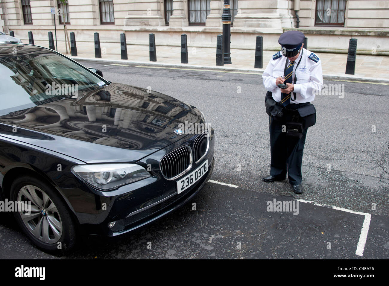 London Traffic warden giving illegally parked BMW a parking ticket. Westminster, London - Stock Image